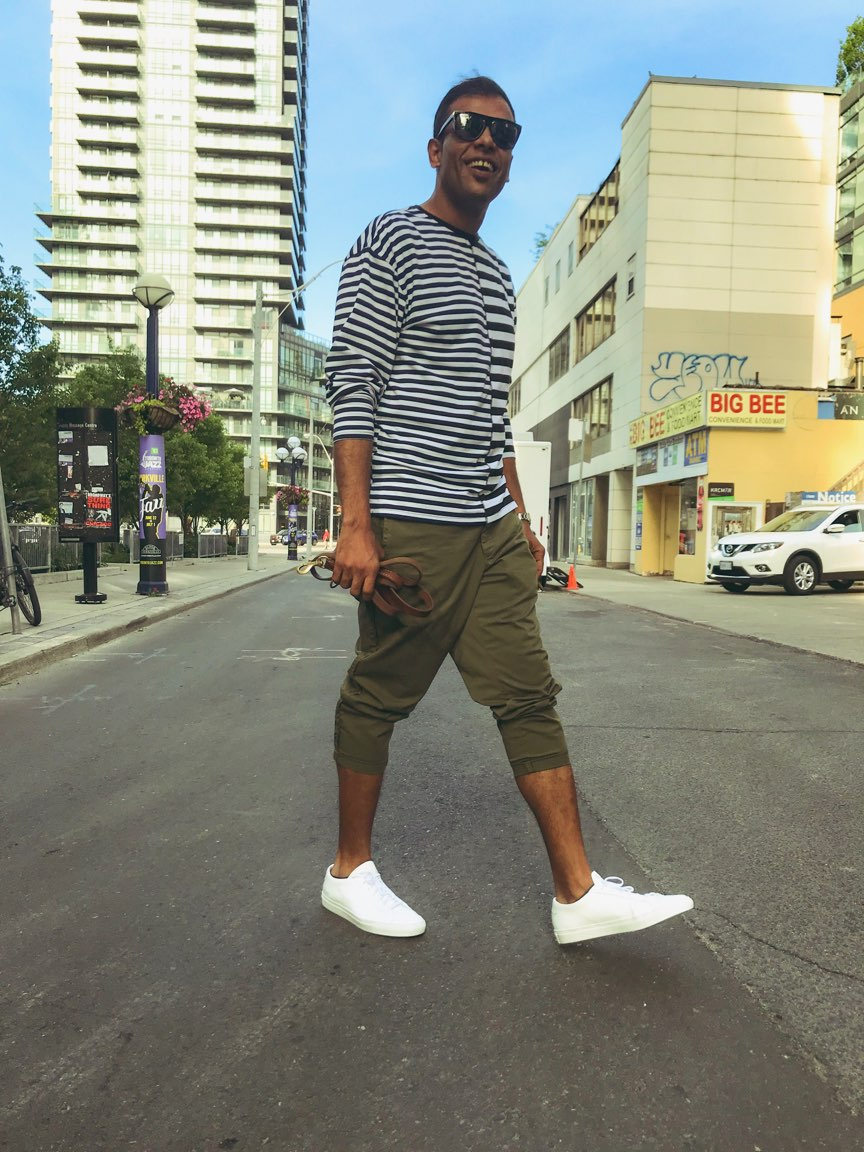 Tall Dark Handsome Man in white shoes walking down the street with buildings and condos and cars in the background